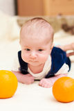 Baby lying on the bed with oranges Royalty Free Stock Photo