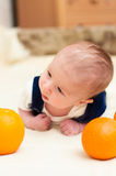 Baby lying on the bed with oranges Royalty Free Stock Image