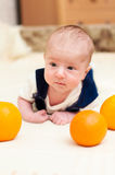 Baby lying on the bed with oranges Royalty Free Stock Photography