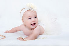 Baby lying in bed with a pearl necklace Stock Photography