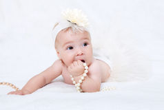 Baby lying in bed with a pearl necklace Stock Image