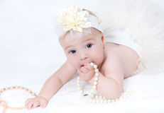 Baby lying in bed with a pearl necklace Royalty Free Stock Images