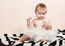 Baby lying in bed with a pearl necklace Stock Photos