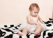 Baby lying in bed with a pearl necklace Royalty Free Stock Image