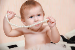 Baby lying in bed with a pearl necklace Stock Images