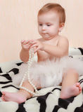Baby lying in bed with a pearl necklace Royalty Free Stock Photo