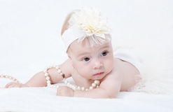 Baby lying in bed with a pearl necklace Royalty Free Stock Photography