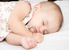 Baby lying on a bed while sleeping in a bright room Stock Photos