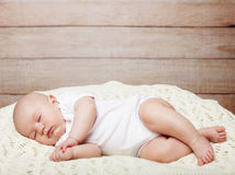 Baby lying on a bed while sleeping Royalty Free Stock Images