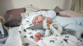 Baby lying on the bed in the sliders and cap, sweet dream cute boy, child hugging a toy while sleeping, Small child stock video