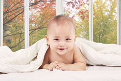 Baby lying on bedroom under blanket Royalty Free Stock Image
