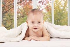 Baby lying on bedroom under blanket Royalty Free Stock Image