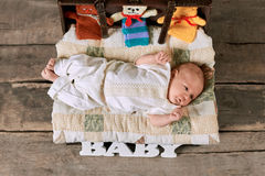 Baby lying on a blanket. Opened suitcase with small child Stock Images