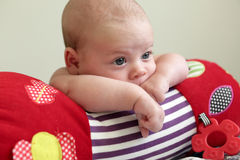 Baby lying on a crawling roll Stock Images