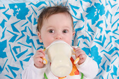 Baby lying in crib and drinking milk from a bottle Stock Image