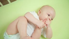 Baby Lying in a Crib at Home Eating its Toes Royalty Free Stock Images
