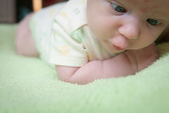 Baby Lying With a Crossed Eyes on  Green Blanket for Tummy Time Stock Images