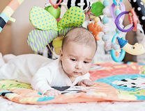 Baby lying on Developing rug. Playing in Mobile. educational toys. Sweet child Crawling And Playing With Toys On Carpet stock images