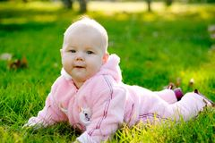 Baby lying on grass. Smiling and looking at camera royalty free stock photos