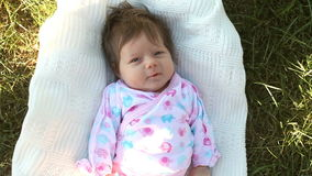 Baby lying on the grass stock footage