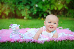 Baby lying on green grass in the park Stock Photos
