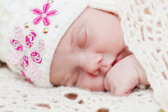 Baby lying in hat on bed under soft white knitted shawl Royalty Free Stock Photos