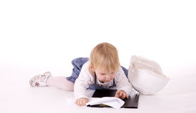 Baby lying, with helmet, reading plans Royalty Free Stock Photo