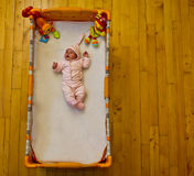 Baby lying in her bed Stock Photography