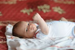 Baby lying on his back on the bed royalty free stock photo
