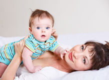 Baby lying on his mom Stock Photos