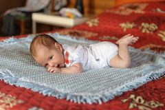 Baby is lying on his stomach stock photo