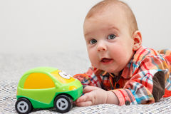 Baby lying on his stomach and plays with green machine Royalty Free Stock Images