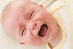 Baby lying indoors crying Royalty Free Stock Photos