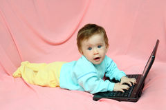 Baby lying with laptop Stock Image