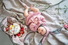 Baby lying on linen blanket and wearing a hat in the form of a Easter bunny with eggs willow branches and Easter pie royalty free stock image