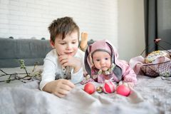 Baby lying on linen blanket and wearing a hat in the form of a Easter bunny with her brother near eggs willow branches stock photos