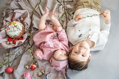 Baby lying on linen blanket and wearing a hat in the form of a Easter bunny with her brother near eggs willow branches stock photography