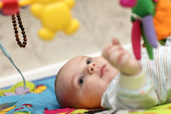 Baby lying on mat Stock Photo