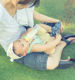 Baby lying on mother's lap while drinking milk from bottle. Royalty Free Stock Photo