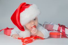 Baby lying with presents in santa hat on grey background Stock Image