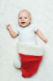 Baby is lying in the Santa's hat Stock Photos