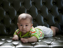 Baby lying on sofa bed with eyes contact to camera Royalty Free Stock Images