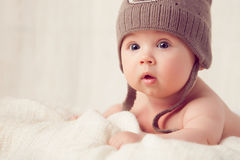 Baby lying on a soft bed cover. With cap Royalty Free Stock Photo