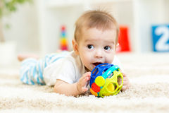 Baby lying on soft carpet in children room royalty free stock photo
