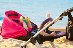 Baby lying in stroller on the beach Stock Photos