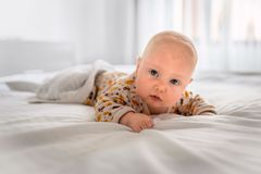 The baby is lying on the white bed royalty free stock image