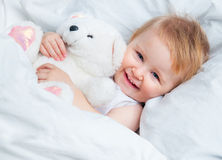 Baby lying in a white bed Stock Image