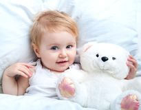 Baby lying in a white bed Royalty Free Stock Image