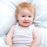 Baby lying in a white bed Stock Photo