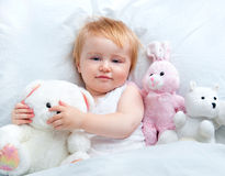 Baby lying in a white bed Stock Images